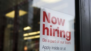 """In this Jan. 4, 2019, file photo, a """"now hiring"""" sign hangs on the door of a Staples store in New York City."""