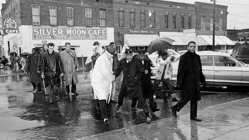 In this March 1, 1965 file photo Dr. Martin Luther King Jr. hops over a puddle as it rains in Selma, Ala. King led hundreds of African Americans to the court house in a voter registration drive.
