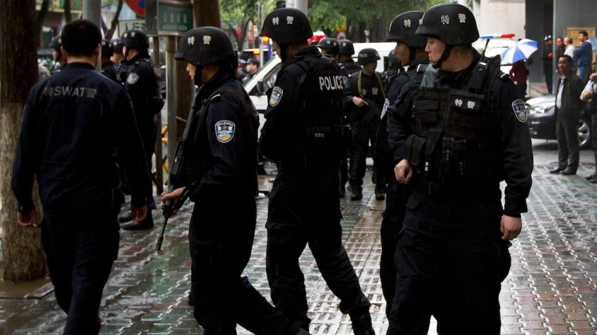 In this May 22, 2014 photo, armed policemen prepare to patrol near the site of an explosion in Urumqi, northwest China's Xinjiang Uygur Autonomous Region.