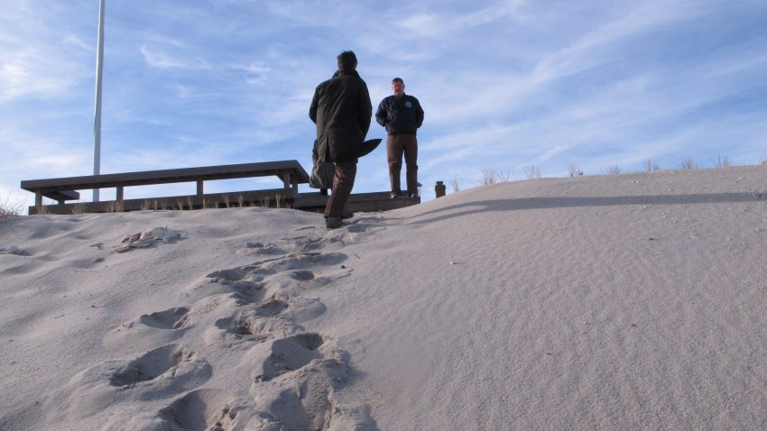 two people stand on a sand dune
