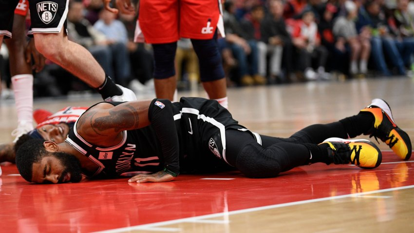Brooklyn Nets guard Kyrie Irving lies on the court after injury