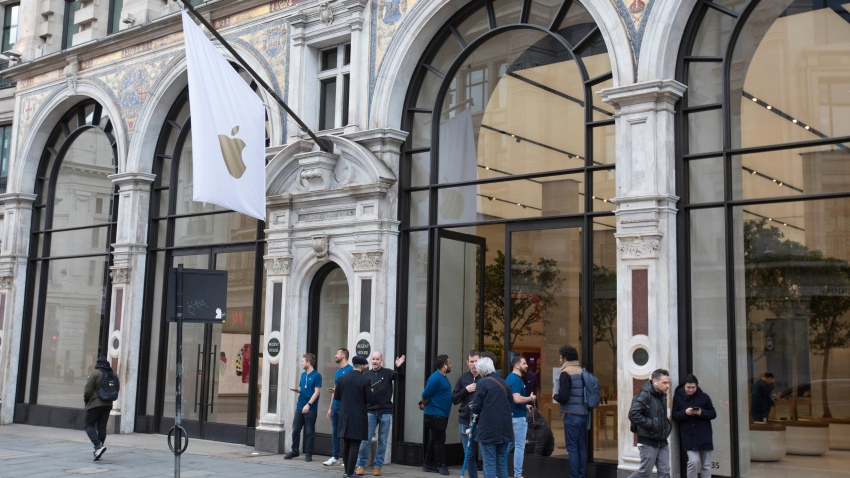Members of staff stand outside of the Apple Store informing people of their closure, on Regent Street, London, Saturday, March 14, 2020.