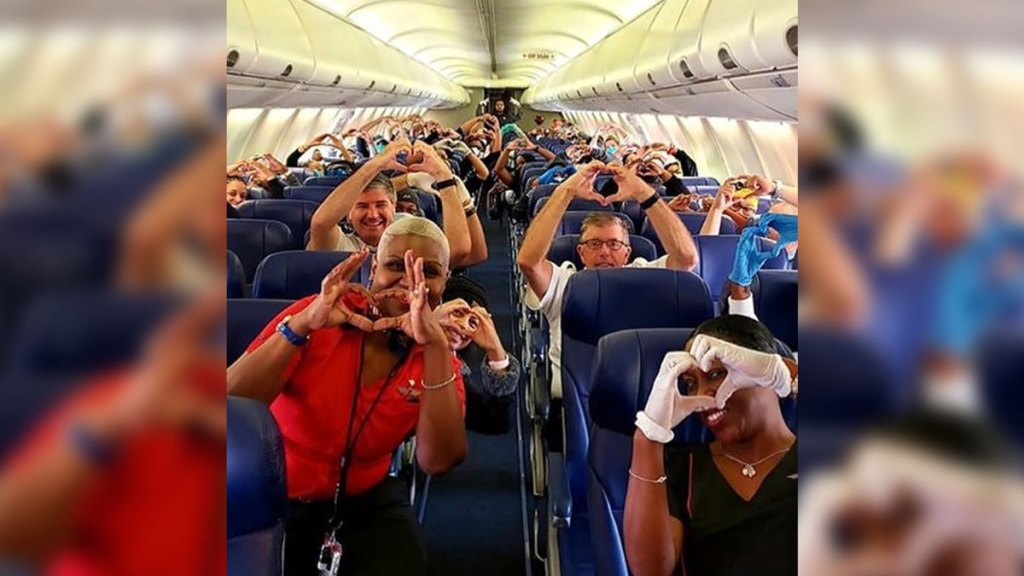 This Friday, March 27, 2020, photo provided by Southwest Airlines employee Dayartra Etheridge shows health care workers, other passengers and flight crew aboard a Southwest flight from Atlanta to New York's LaGuardia Airport holding their hands in the shape of a heart