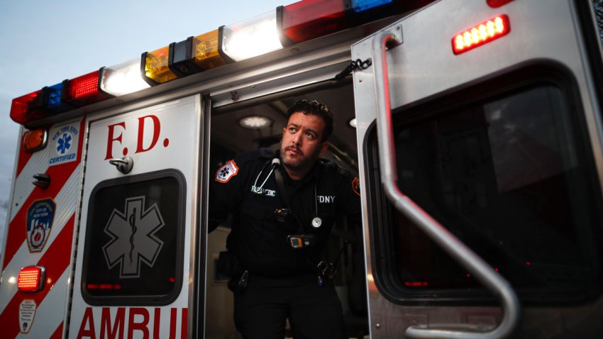 """In this April 23, 2020, photo FDNY paramedic Alex Tull, who has recently recovered from COVID-19, prepares to begin his shift outside EMS station 26, the """"Tinhouse"""", in the Bronx borough of New York."""