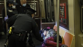 officers approach a person sleeping on a subway train