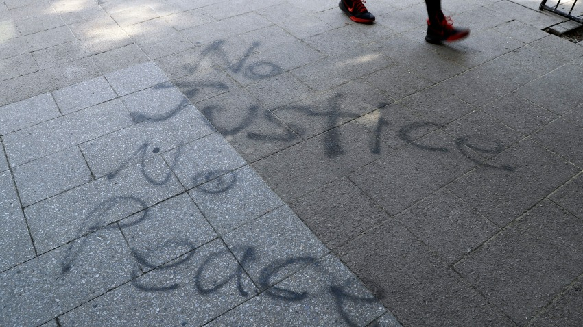 """A man walks past """"No Justice No Peace"""" spray painted on a sidewalk in downtown Louisville, Ky., June 2, 2020."""
