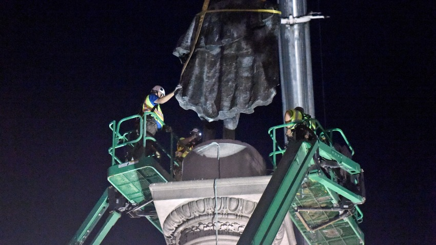 Crews use cranes to affix straps to a statue of former vice president and slavery advocate John C. Calhoun as part of the process of removing it from a 100-foot-tall monument in downtown Charleston, S.C., on Wednesday, June 24, 2020.