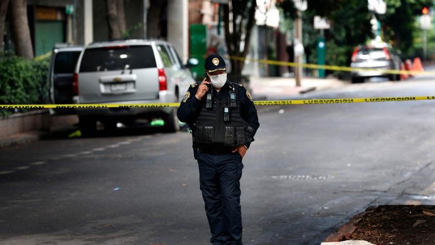 An abandoned vehicle that is believed to have been used by gunmen in an attack against the chief of police is sealed off with yellow tape and guarded by police, in Mexico City.