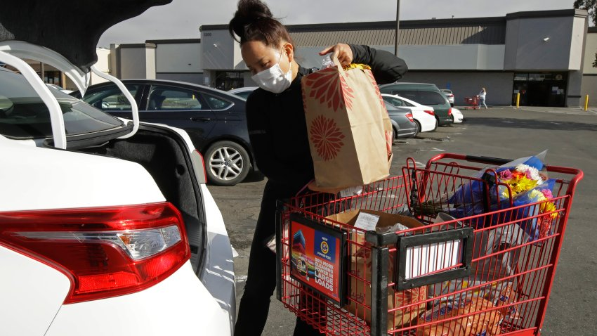 Instacart worker Saori Okawa loads groceries into her car for home delivery