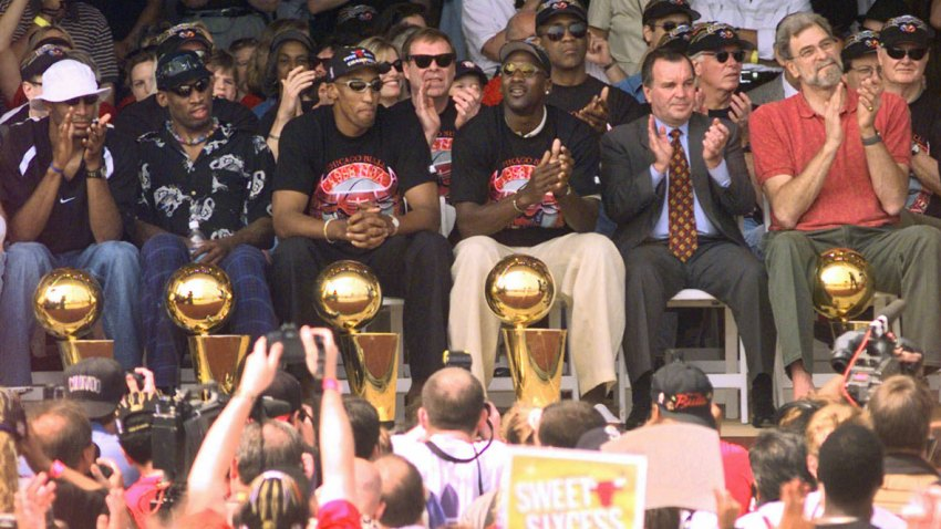 In this June 16, 1998, file photo, NBA Champions (from left) Ron Harper, Dennis Rodman, Scottie Pippen, Michael Jordan and coach Phil Jackson are joined on stage by Chicago Mayor Richard Daley, second from right, during a city-wide rally in Chicago, Ill.