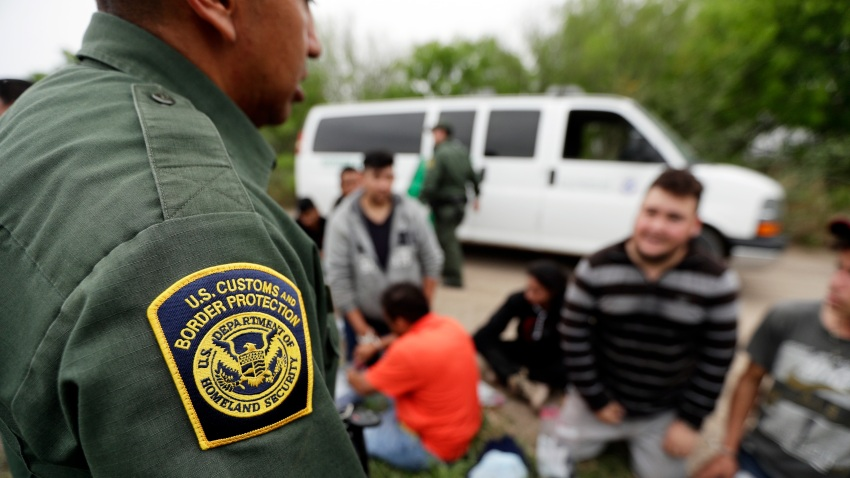 In this Thursday, March 14, 2019, file photo, a Border Patrol agent talks with a group suspected of having entered the U.S. illegally near McAllen, Texas.