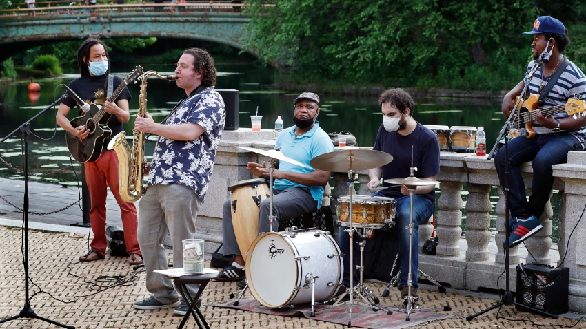 In this Thursday, June 18, 2020, photo, Alegba Jahyile, left, leader of Alegba and Friends, a Haitian roots/jazz band, and saxophonist Mark Kraszewski, second from left, play a set with other musicians in a free nightly concert at Brooklyn's Prospect Park boathouse in New York. From left are Jahyile, Kraszewski, percussionists Alix Julien and John Czolacz, and Lamarre Junior on bass.