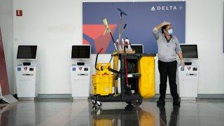A worker cleans the Delta self check-in kiosks at Ronald Reagan Washington National Airport, May 5, 2020 in Arlington, Virginia.