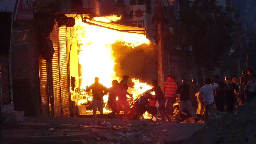 A shop burns as a mob sets it on fire during violence between two groups in New Delhi, India, Tuesday, Feb. 25, 2020. At least 10 people were killed in two days of clashes that cast a shadow over U.S. President Donald Trump's visit to the country.