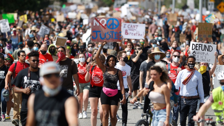 Desiree Wallace, center, of Denver, holds a placard while moving with fellow demonstrators down Sable Boulevard during a rally and march over the death of 23-year-old Elijah McClain, Saturday, June 27, 2020, in Aurora, Colo. McClain died in late August 2019 after he was stopped while walking to his apartment by three Aurora Police Department officers.