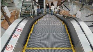Mall shoppers riding up an escalator