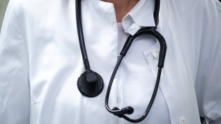 A doctor in a white lab coat wears a stethoscope around their neck