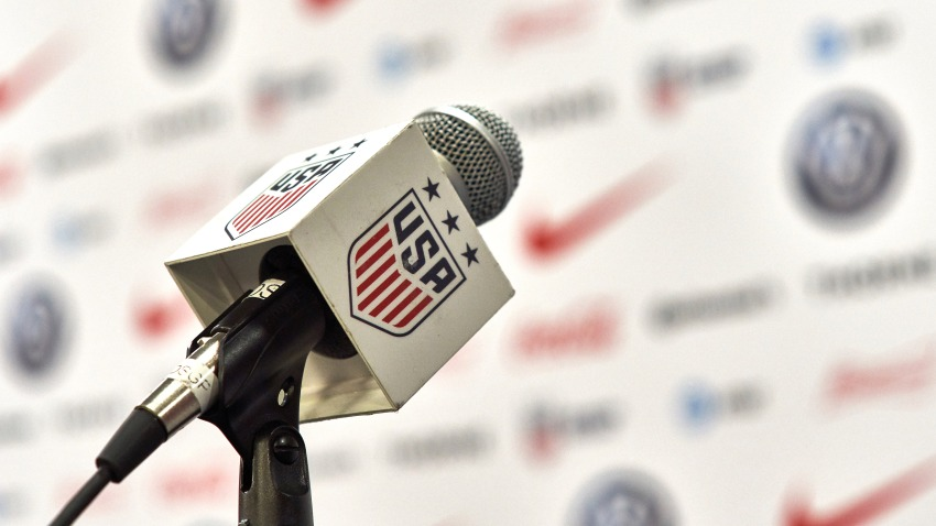 A detailed view of a press conference microphone is seen with the USA Soccer Federation logo.