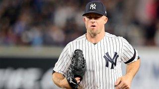 Yankees player Brett Garnder in a pinstripe Yankee uniform and hat wearing a baseball glove