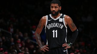 Kyrie Irving wearing a dark Brooklyn Nets uniform with his number 11 emblazoned on his shirt.