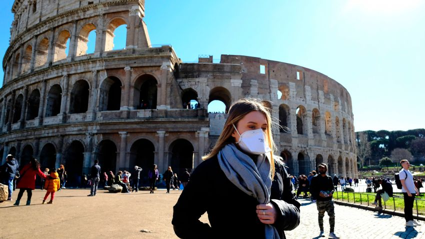 Tourist wearing a protective respiratory mask tours outside the Colosseo monument in Rome, Italy.