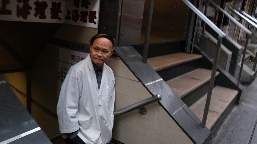 a restaurant worker stands in the street in New York's Chinatown in New York City