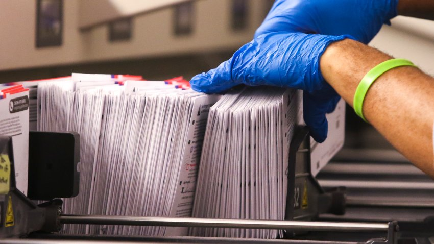 An election worker handles vote-by-mail ballots