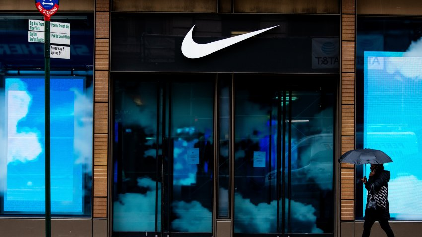 A pedestrian holding an umbrella passes in front of a closed Nike Inc. store in the SoHo neighborhood of New York, U.S., on Tuesday, March 17, 2020.