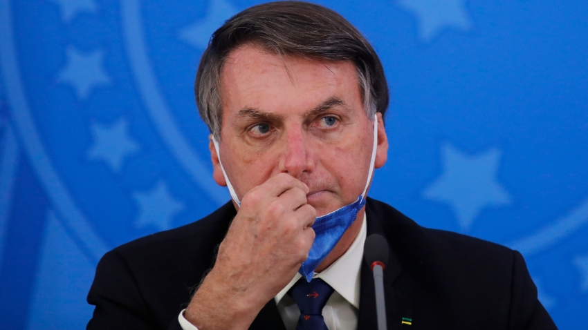 In this March 20, 2020, photo, Brazil's President Jair Bolsonaro attends a press conference on the coronavirus pandemic at the Planalto Palace in Brasilia, Brazil.