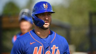 Tim Tebow wearing a blue and orange Mets uniform and helmetGetty