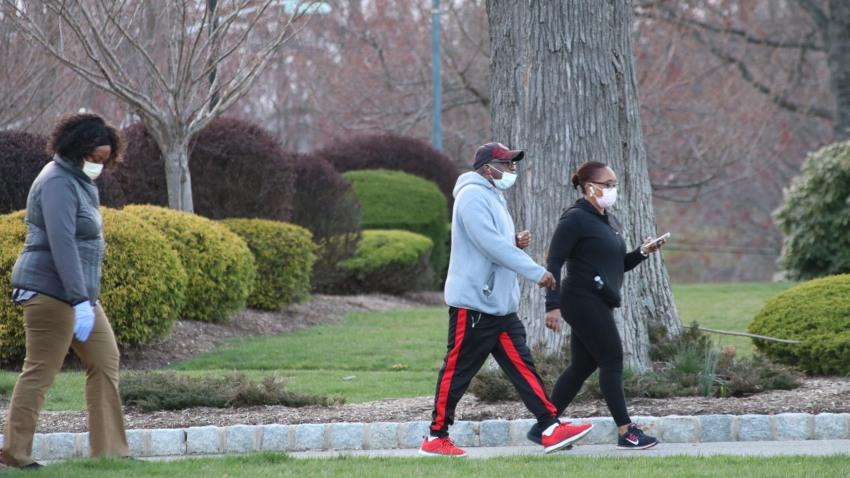 People, wearing medical masks as a precaution against the new type of coronavirus (COVID-19) pandemic, walk through the road at Eagle Rock Reservation Park in New Jersey, United States on April 7, 2020.