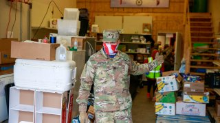 A member of the Indiana National Guard wearing a balaclava supports volunteer workers in distributing food at Pantry 279 to help those experiencing food insecurity during the COVID-19/Coronavirus stay-at-home order. Hoosiers have been ordered to only travel for essential needs.