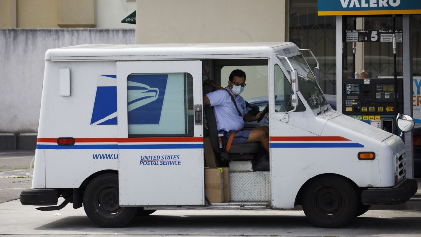 A U.S. Postal Service mail carrier wearing a protective mask closes a vehicle door after refueling in Hawthorne, California, on April 20, 2020.