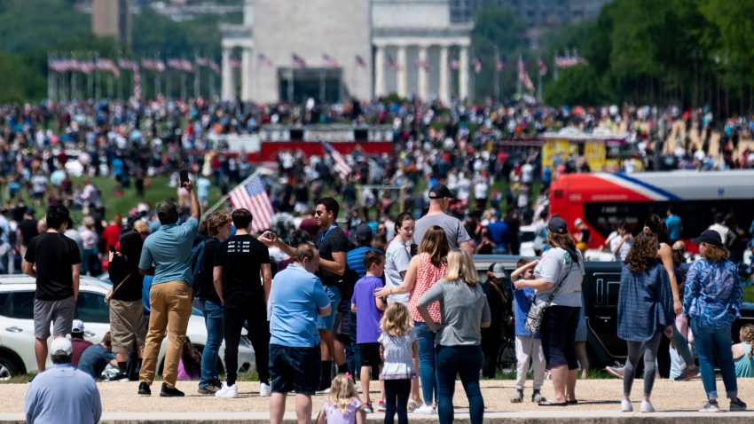 A large crowd gathers on the National Mall to watch the Navy's Blue Angels and the Air Force's Thunderbirds conduct a flyover of Washington, D.C