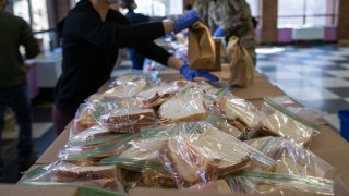 Volunteers put together meals for distribiution
