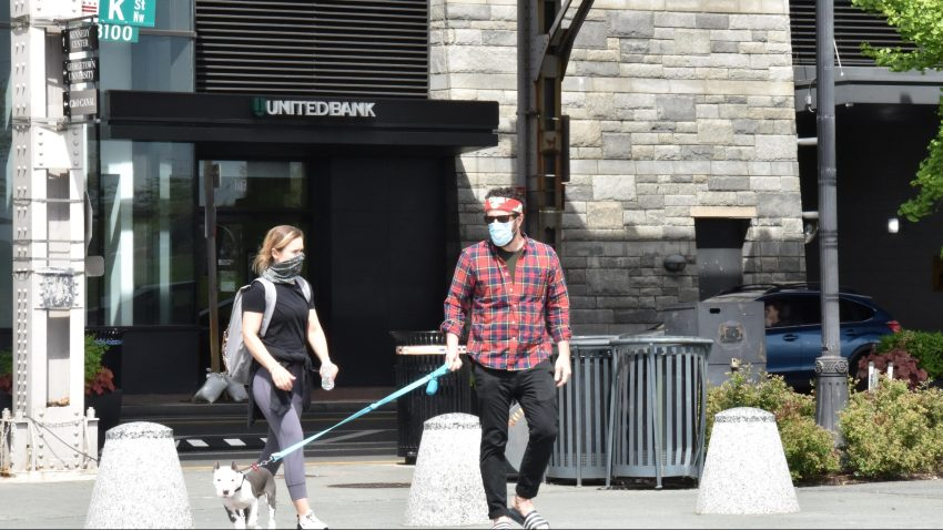 People wearing face masks walk a dog amid novel coronavirus outbreak on April 12, 2020, in Washington, DC.