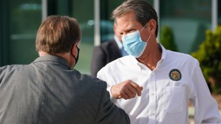 Brian Kemp, governor of Georgia, wears a protective mask while bumping elbows with an attendee during a 'Wear A Mask' tour stop in Dalton, Georgia, on July 2, 2020.