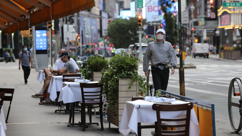 A person walks by tables placed outside for outdoor dining at a Serafina restaurant in midtown