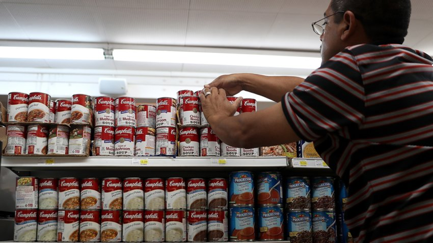 In this file photo, a worker arranges cans of Campbell's soup on a supermarket shelf on May 20, 2016 in San Rafael, California.