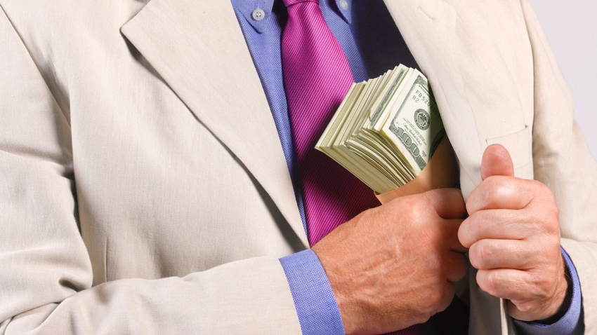 FILE - A man hides a stack of US Dollars in his jacket pocket.