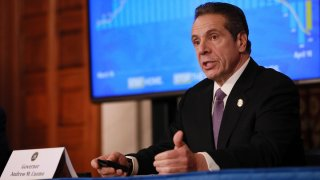 Gov. Andrew Cuomo sitting behind a desk during his daily coronavirus press briefing.
