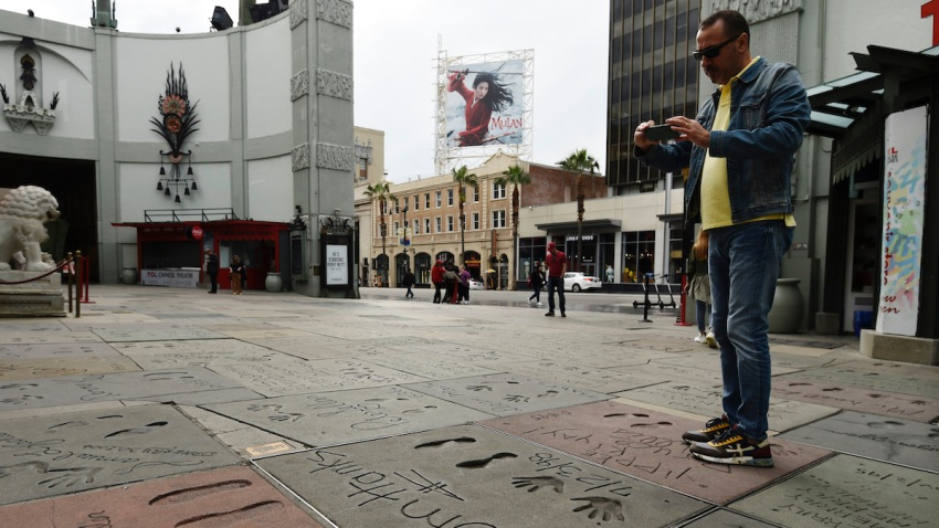 A man takes a picture of the hand and footprints of actor Tom Hanks in the forecourt of the TCL Chinese Theatre