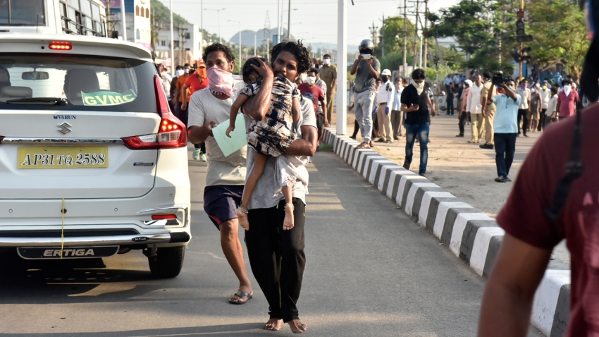 A man runs carrying a child affected by a chemical gas leak in Vishakhapatnam, India, Thursday, May 7, 2020. Chemical gas leaked from an industrial plant in southern India early Thursday, leaving people struggling to breathe and collapsing in the streets as they tried to flee.