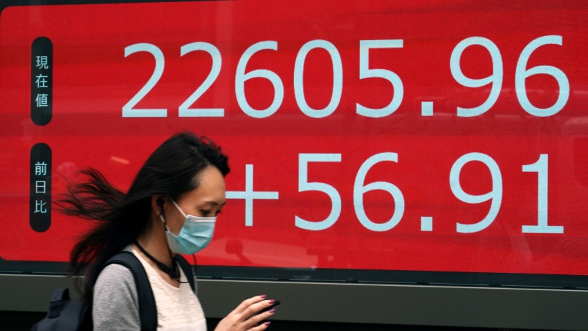 A woman walks past an electronic stock board showing Japan's Nikkei 225 index at a securities firm in Tokyo Wednesday, June 24, 2020.
