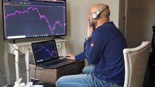 In this April 6, 2020, file photo provided by Meric Greenbaum, a Designated Market Maker with IMC works in his home office in Shelter Island, New York.