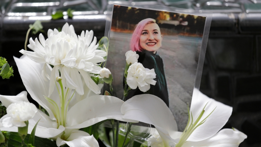 A photo of Summer Taylor, who suffered critical injuries and died after being hit by a car while protesting over the weekend, sits among flowers at the King County Correctional Facility where a hearing was held for the suspect in their death Monday, July 6, 2020, in Seattle. Dawit Kelete is accused of driving a car on to a closed Seattle freeway and hitting two protesters, killing one, over the weekend.