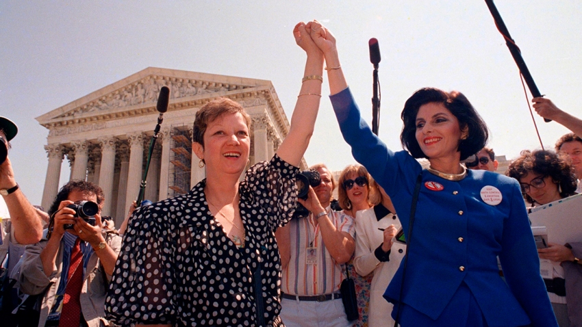 In this April 26, 1989, file photo, Norma McCorvey, Jane Roe in the 1973 court case, left, and her attorney Gloria Allred hold hands as they leave the Supreme Court building in Washington after sitting in while the court listened to arguments in a Missouri abortion case.