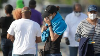 A person pauses as she gets in line at a walk-up coronavirus testing site during the COVID-19 pandemic, Saturday, April 18, 2020, at the Urban League of Broward County in Fort Lauderdale, Fla.