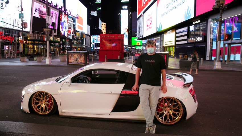 """In this Saturday, May 2, 2020, file photo, Danny Lin poses with his 2008 Audi R8 in New York's Times Square during the coronavirus pandemic. """"I never bring my car here,"""" said the 24-year-old from Queens. """"Only for today, to get some cool shots."""""""