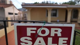 File photo - A for sale sign is posted in front of a home on Nov. 17, 2016, in Miami, Florida.